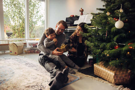 Parents giving gifts to their son during Christmas. Father giving Christmas present to a his soy while sitting by Christmas tree.