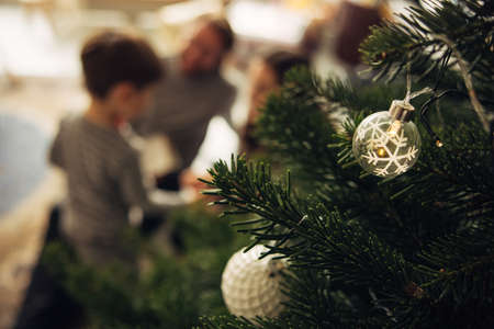 Close-up of a decorated Christmas tree with family sitting in background at home. Christmas tree decorated with baubles in living room. Stock fotó