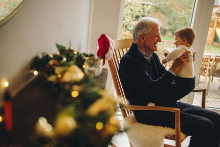 Elderly man with his grandson on a christmas eve. Grandfather holding his grandson sitting on chair.