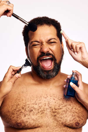 Many hands grooming beard man. Hands of women with makeup brush, razor, cream and perfume bottle grooming an excited man. Stock fotó