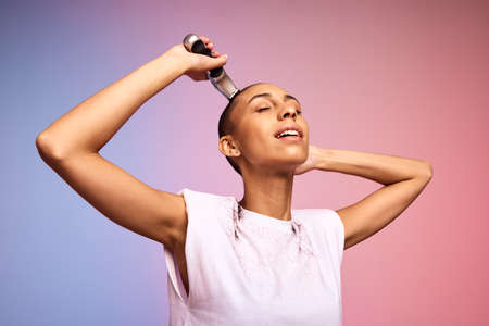 Strong female shaving her head using trimmer. Woman cutting her hair using trimmer on colorful background. Stock fotó