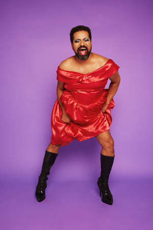 Gender queer male performing on purple background. Drag queen wearing a shiny dress singing in theater. Stock fotó