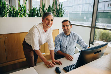 Happy manager and coworker working together and looking at camera. Businesswoman with coworker smiling at camera in office