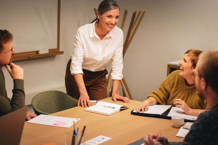 Smiling businesswoman talking with team and smiling during meeting. Group of business professionals having a meeting in office boardroom.