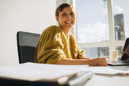 Confident businesswoman sitting at desk and looking at camera. Cheerful female executive sitting at desk and smiling in office.