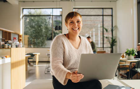Smiling female entrepreneur sitting in co-working space using laptop. Cheerful female executive in office with laptop.