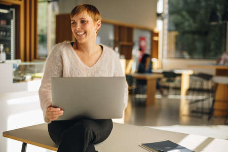 Freelancer with a laptop sitting in coworking space. Businesswoman looking away and smiling. Stok Fotoğraf