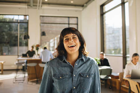 Portrait of happy freelancer standing in co-working space with people working in background. Happy businesswoman laughing in office. Stok Fotoğraf