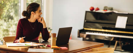 Woman designer working from home. Illustrator sitting at home with laptop and digital tablet looking away and smiling. Stok Fotoğraf