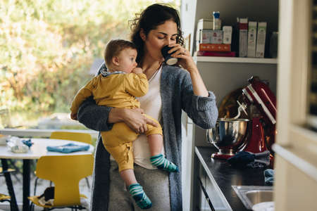 Woman with baby drinking coffee in kitchen. Mother carrying her infant having a cup of coffee.