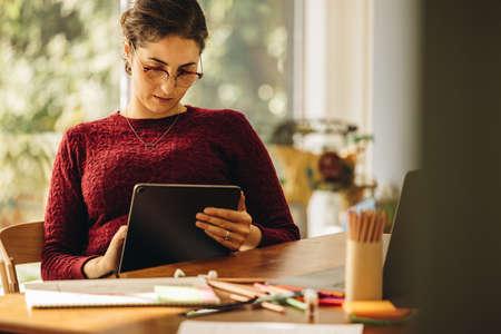 Female designer using graphic tablet for making illustrations. Freelance illustrator working from home.