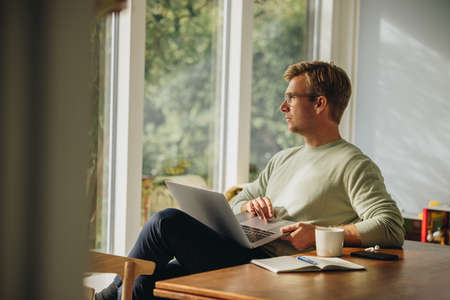 Man sitting with laptop at home and looking away. Business man working form home. Stok Fotoğraf