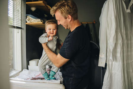 Father getting his son ready at home. Man at maternity leave taking care of his new born baby.
