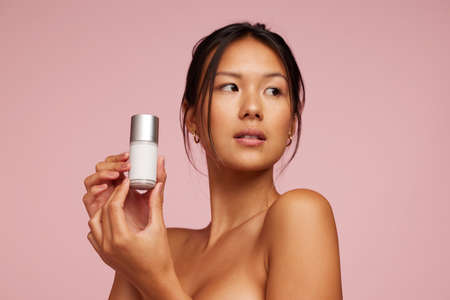 Beautiful asian woman holding beauty care product. Female model presenting cosmetic product and looking away.