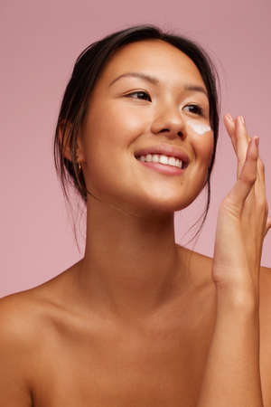 Woman applying face cream and smiling. Asian female putting some moisturizer on her face looking away and smiling.