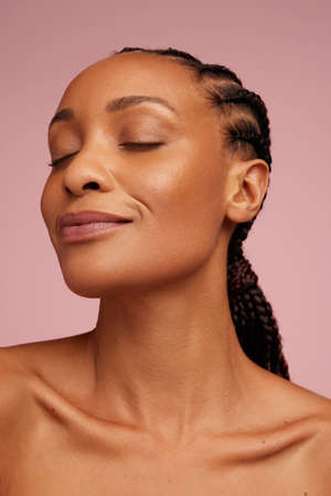 Close-up of a woman with eyes closed on pink background. African american female with healthy skin. Stok Fotoğraf