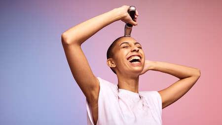 Woman shaving her head feeling strong and powerful on colorful background. Cheerful female using a hair clipper on her head.