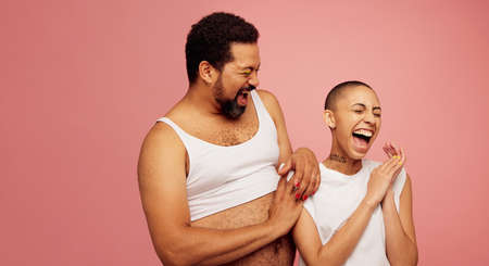 Gay male with friend smiling on pink background. Cheerful friends standing together.
