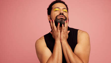 Genderqueer male with yellow eye shadow makeup standing on pink background. Gender fluid man in black t-shirt with his eyes closed.