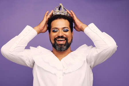 Portrait of drag queen with crown on head. Flamboyant genderqueer in female outfit wearing makeup and crown.