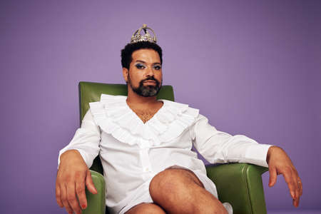 Confident drag queen sitting on arm chair. Man with beard wearing female outfit, makeup and crown looking at camera on purple background.