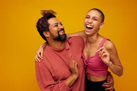 Non confroming friends standing together on yellow background. genderqueer man and woman smiling together. Stok Fotoğraf