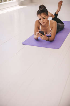 Woman watching yoga instructions from an app on her smart phone. Female lying on yoga mat using mobile phone. Stok Fotoğraf