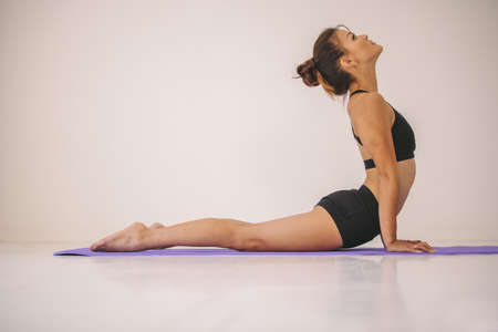 Side view of woman doing core stretch on fitness mat. Young female in sportswear practicing Cobra pose yoga asana at gym. Stok Fotoğraf