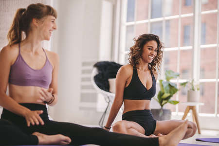 Young female relaxing and talking after workout session. Female friends during yoga class break at fitness center.