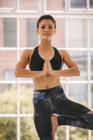 Fitness woman practicing yoga tree pose meditation. Female with hands joined and standing with one leg at yoga class.