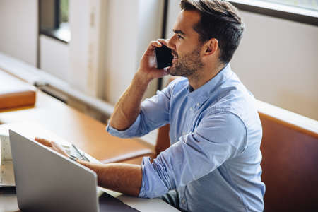Man talking on mobile phone at desk in office. Businessman sitting at desk and speaking on smart phone.