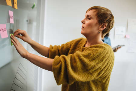 Female executive putting sticky note on glass. Businesswoman pasting adhesive note on glass for planning strategy.