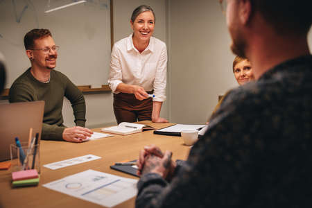 Executive female inviting questions after business presentation in boardroom meeting with colleagues. Manager explaining new project with colleagues in meeting.