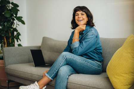 Happy businesswoman on couch in office. Cheerful freelancer relaxing in office lobby looking at camera and smiling.