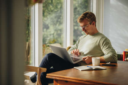 Man sitting at home using laptop. Man searching some information on laptop computer. Stok Fotoğraf