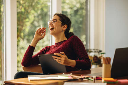 Cheerful designer sitting at home with digital tablet. Woman looking away and laughing while making illustrations on tablet computer.