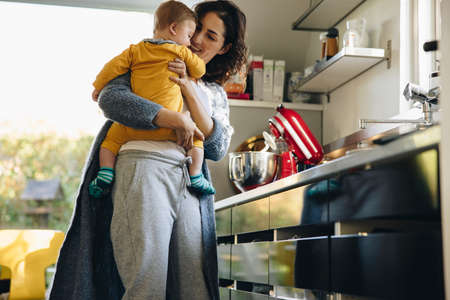Young mom enjoys her time on maternity leave with her baby. Woman with toddler in kitchen. Stok Fotoğraf