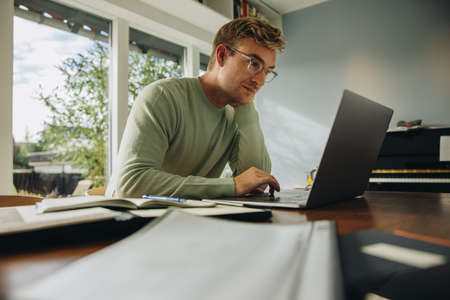 Business man using laptop at home office. Man sitting at table looking busy working on laptop. Stok Fotoğraf