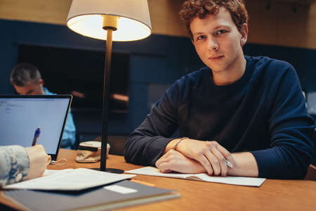 Portrait of university student in library looking at camera. Relaxed young male sitting at library desk.
