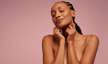 Close-up of a natural beauty on pink background. Woman with flawless skin.