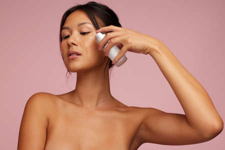 Asian woman using serum on her face. Beautiful woman applying oil to her face. Stok Fotoğraf