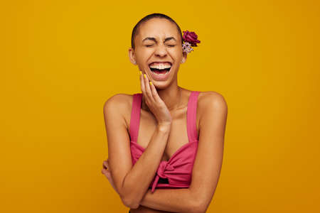 Cheerful woman with short hair. Woman in fashionable top wearing flowers on head laughing on yellow background.