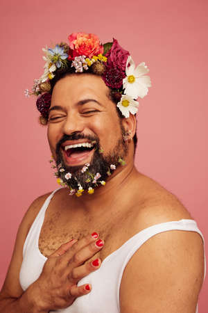 Smiling queer wearing makeup and tank top. Cheerful drag queen wearing flowers in his head and beard. Stok Fotoğraf