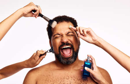 Hands of women shaving, applying makeup and cologne to excited bearded person. Man shouting with joy while being groomed by many hands on white background.