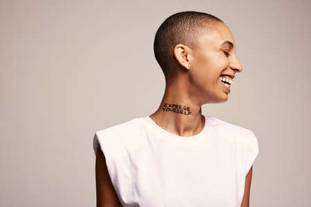 Side view of bald woman feeling happy. Smiling woman with shaved head and express yourself written on her neck.