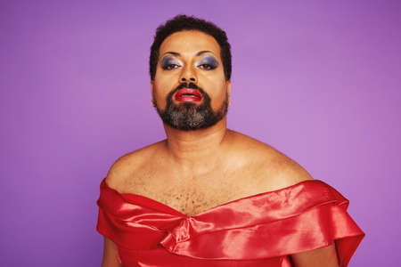 Portrait of a man with beard wearing red female dress and makeup. Elegant drag queen on purple background. Stock fotó