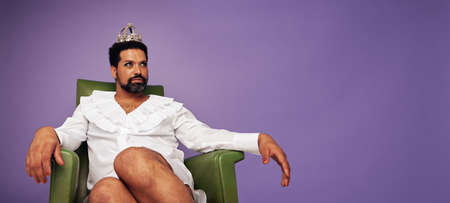Attractive drag queen sitting on arm chair and looking away. Man with beard in woman clothing, makeup and crown on purple background.