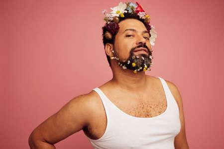 Drag queen wearing flowers. Bearded man wearing tank top posing on pink background