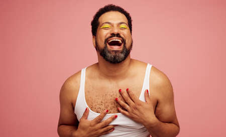 Gender fluid male in a female top and makeup. Bearded man wearing eye shadow and nail polish laughing on pink background