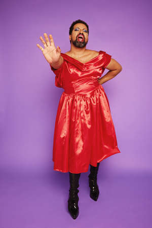 Gender fluid person in dress singing in studio. Gay man performing in shiny red dress on purple background.